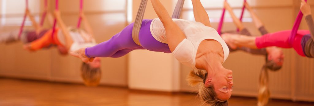 Mehrere Personen in Aerial Yoga Tüchern