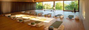 Yogaraum mit Holzboden, Matten, Kissen und Sandsack